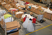 "Pictured: Staff members, Jonathan Beasley and Jo Williams pictured amongst the box pallets full of wedding dresses on offer at John Pye Auctions in Pyle, south Wales, UK.<br /> Re: A bride cried tears of joy after her missing wedding dress was found among a pile of 20,000 gowns in a warehouse.<br /> Meg Stamp, 27, paid £1,300 for the beautiful ivory lace dress but it  was seized by liquidators after a bridal company went bust.<br /> It was boxed up along with 20,000 others and due to be sold for a knock-down price at auction.<br /> But determined Meg banged on the auctioneer door saying: ""I want my dress back"".<br /> Staff at John Pye auctioneers in Port Talbot spent three hours sifting through boxes until they finally found Meg's dream dress."