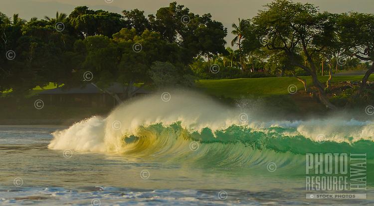 At sunrise, a wave creates a perfect barrel by the Mauna Kea Golf Course, North Kohala Coast, Big Island.