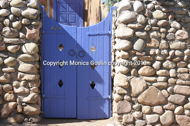 A bright blue wooden gate between a stone wall on Canyon Road in Santa Fe, New Mexico.