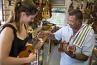 Woman trying out an ukulele at Mele Ukulele store in Wailuku, Maui