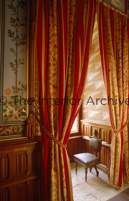 A chair in a window alcove is framed by a pair of grand curtains