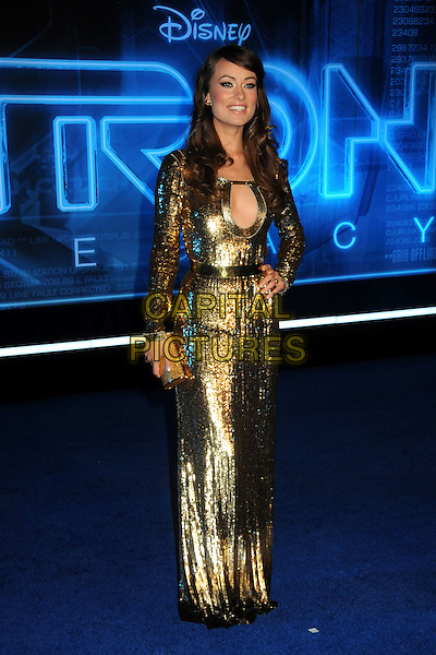 "OLIVIA WILDE .""TRON: Legacy"" L.A. Premiere held at the El Capitan Theatre, Hollywood, California, USA, 11th December 2010..full length clutch bag shiny gold cut out sequined sequin dress long sleeve maxi hand on hip .CAP/ADM/BP.©Byron Purvis/AdMedia/Capital Pictures."