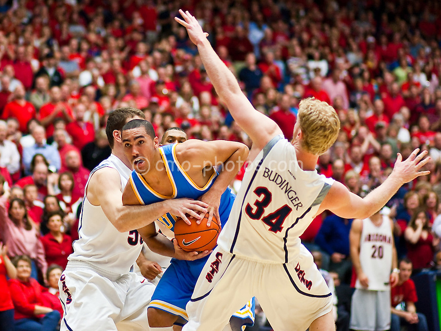 Feb 14, 2009; Tucson, AZ, USA; Arizona Wildcats center Alex Jacobson (50) ties up UCLA Bruins forward Drew Gordon (0) when Gordon ran into forward Chase Budinger (34) in the second half of a game at the McKale Center.   The Wildcats won the game 84-72 to break an eight-game losing streak against the Bruins and win their seventh game in a row.