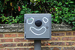 Graffiti funny face drawn on grey street furniture box, Oxford, England, UK
