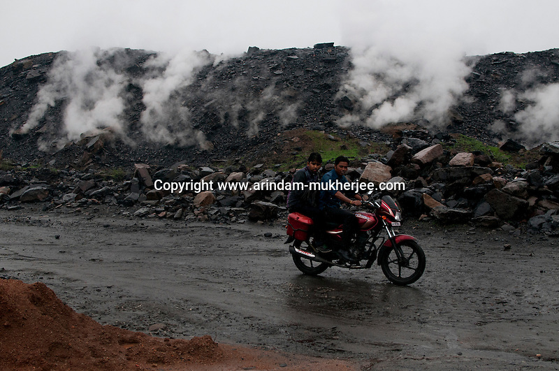 A motor bike passes through the poisonous gases and fumes generating from burning coal seam beneath the surface. The roadways are also affected in and around Jharia. Government is trying to divert these roads through safe lands. A huge coal mine fire is engulfing the city of Jharia from all its sides. All scientific efforts have gone in vain to stop this raging fire. This fire is affecting lives of people living in and around Jharia. Jharkhand, India. Arindam Mukherjee