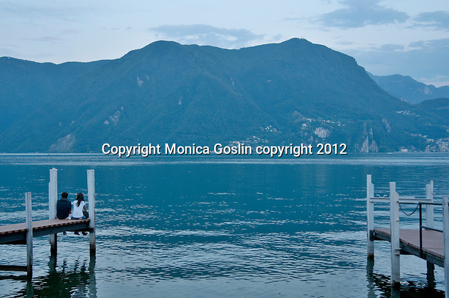 A young couple sit at the end of a dock on Lake Lugano, Switzerland at dusk
