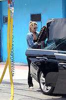 Ali Larter clutches her Louis Vuitton bag and pays the car wash services. Los Angeles, California on 04.05.2012..Credit: Correa/face to face.. /MediaPunch Inc. ***FOR USA ONLY***