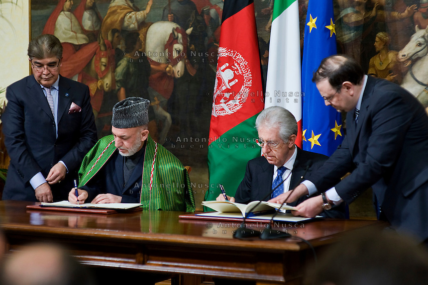 Il Presidente dell'Afghanistan Hamid Karzai con Mario Monti a Palazzo Chigi per la firma del trattato bilaterale tra Afghanistan e Italia..Afghan President Hamid Karzai (L) and Italian Prime Minister Mario Monti shake hands during a meeting to sign a bilateral agreement on cooperation and partnership, at Palazzo Chigi in Rome. Italy is the first western country to have signed a cooperation agreement with Afghanistan.
