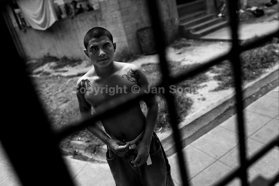 A member of the Mara Salvatrucha gang (MS-13) stands behind the bars in the prison of Tonacatepeque, El Salvador, 18 May 2011. During the last two decades, Central America has become the deadliest region in the world that is not at war. According to the UN statistics, more people per capita were killed in El Salvador than in Iraq, in recent years. Due to the criminal activities of Mara Salvatrucha (MS-13) and 18th Street Gang (M-18), the two major street gangs in El Salvador, the country has fallen into the spiral of fear, violence and death. Thousands of Mara gang members, both on the streets or in the overcrowded prisons, organize and run extortions, distribution of drugs and kidnappings. Tattooed armed young men, mainly from the poorest neighborhoods, fight unmerciful turf battles with their coevals from the rival gang, balancing between life and death every day. Twenty years after the devastating civil war, a social war has paralyzed the nation of El Salvador.