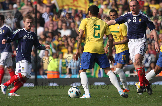 Daniel Alves being closed down by Barry Bannan and Scott Brown
