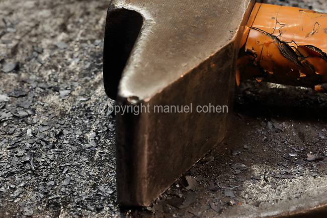 Detail of a steel hammer on a workbench inside the Soleil Rouge workshop of Nicolas Desbons, metalworker and artist, photographed in 2017, in Montreuil, a suburb of Paris, France. Desbons works mainly in steel but often in conjunction with other materials such as fibreglass, glass and clay, using both cold metal and forge techniques. He produces both figurative and abstract sculptures as well as furniture and lighting. Picture by Manuel Cohen