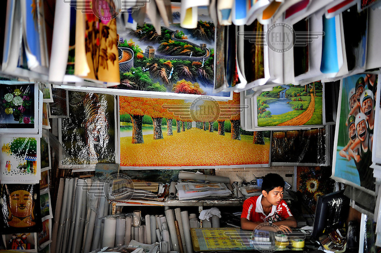 A young man checks a computer in his shop where he sells works of art. Dafen is home to an art industry producing replicas, as well as original works, of pieces by the world's great artists for sale overseas. The success of this business has attracted more and more trained artists to the town seeking an opportunity to make a living.
