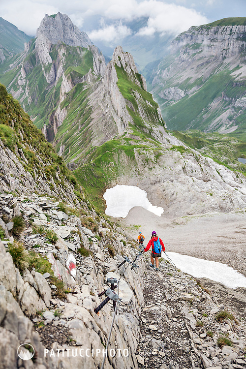 A hiker holding on to a cable on an exposed section of trail in the Alpstein group of Eastern Switzerland, a small, separate from the Alps mountain range ideal for hiking thanks to less rugged, lower terrain.