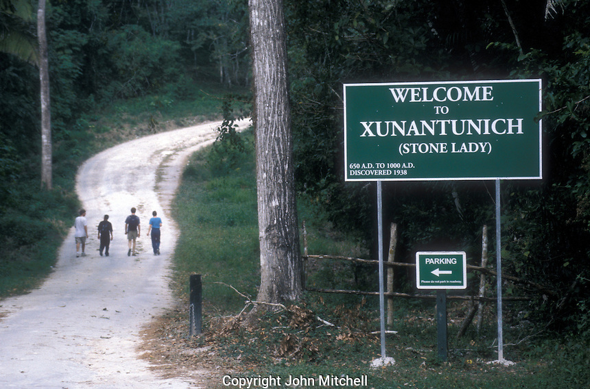 Tourists walking along the road to the Mayan ruins of Xunantunich, Belize, Central America