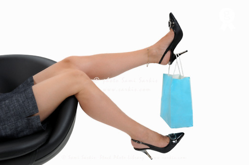Shopping bag hanging on woman's high heels (Licence this image exclusively with Getty: http://www.gettyimages.com/detail/103933323 )