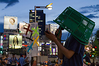 A younger Japanese man wearing a shopping basket on his head speaks at a small protest against the staging of the Olympic Games in Shinjuku, Tokyo, Japan Friday June 30th 2017. Though mostly popular with the Japanese population he staging of the 2020 Olympic Games in Tokyo is felt by some to be a waste of money when the economy is bad, causing increasing poverty rates and with problems in the Tsunami damaged North East coast still not fully resolved.