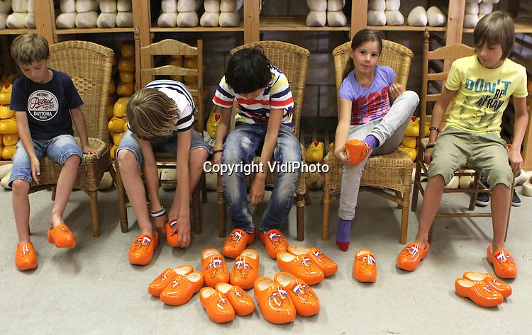 Foto: VidiPhoto..HEINKENSZAND - Kinderen uit het Zeeuwse Heinkenszand staan donderdag in de rij bij Klompenmakerij Traas voor de nieuwste hype: oranje klompen. Nu het Europees Kampioenschap voetbal op het punt staat te beginnen, zijn de oranje klompen bij Traas niet aan te slepen. De bestellingen komen zelfs uit het verre buitenland. Duitsers, Zwitsers en Tsjechen bestellen opmerkelijk genoeg ook oranje klompen. Voor de buitenlandse fans van het Nederlands elftal is Traas de website ?ek-klompen.nl? gestart. En zowel in de winkel als op de website loopt het storm..