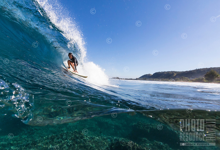 A young woman gets barreled on the North Shore of O'ahu.