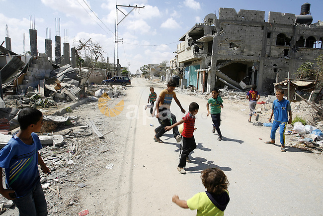 "Palestinian children play near a destroyed house in Khan Yunis in the southern Gaza Strip on September 11, 2014. Israel's deputy foreign minister,Tzahi Hanegbi , warned that Hamas was likely to resume ""violence"" if it feels it has made no political gains from upcoming talks in Cairo. Photo by Abed Rahim Khatib"