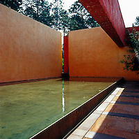 A raised pool at one side of the courtyard is sheltered by monumental coloured walls
