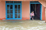A woman watches from the doorway of her home during November 2014 flooding in Meulaboh in Indonesia's Aceh province. Flooding in the region has grown worse because of climate change and the proliferation of palm oil plantations.