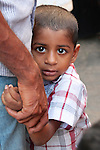 A shy boy clings to his father in a busy market in Kochi.
