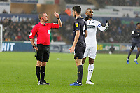 (L-R) Referee David Webb speaks to Morgan Fox of Sheffield Wednesday and Leroy Fer of Swansea City who both protested for a foul awarded to Swansea during the Sky Bet Championship match between Swansea City and Sheffield Wednesday at the Liberty Stadium , Swansea, Wales, UK. Saturday 15 December 2018