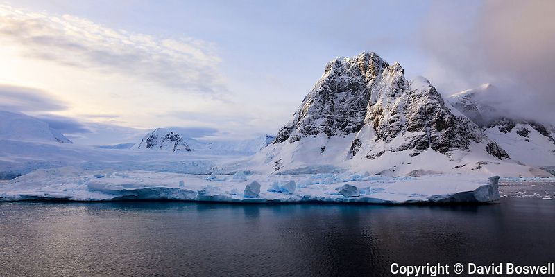 Small peaks, cliffs, and ice abound along the Lemaire Channel on the shore of the Antarctic Peninsula.