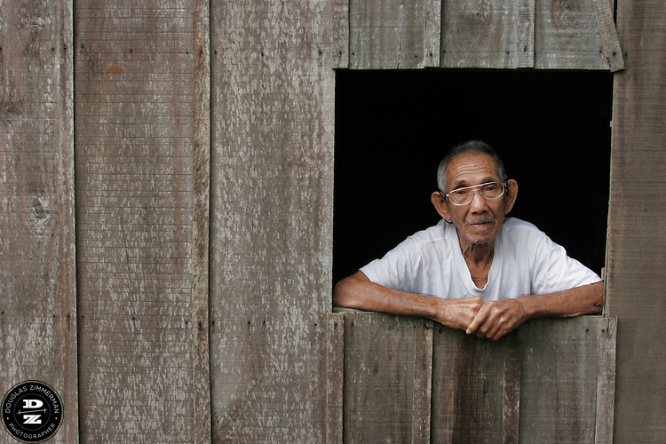 A man rests at a window at his floating river house in Chau Doc on the Bassac River in the Mekong Delta in Vinh Long, Vietnam.  The Mekong Delta has long been the watery  thoroughfare for the many villages that dot the riversides of the delta.  Many of the villages have floating markets where people can buy produce and other items from wholesalers.  Photograph by Douglas ZImmerman