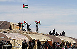 "Palestinian activists fix flags on a tent in an ""outpost"" named Bab al-Shams (""Gate of the Sun"") that they set up between Jerusalem and the Jewish settlement of Maale Adumim in the Israeli-occupied West Bank, in an area where Israel has vowed to build new settler homes, on January 12, 2013. The Israeli occupation administration gave Palestinian activists an ultimatum to quit the protest camp in part of the West Bank, but hours after the deadline passed, there was no sign of any Israeli move to evict the protesters. Photo by Issam Rimawi"