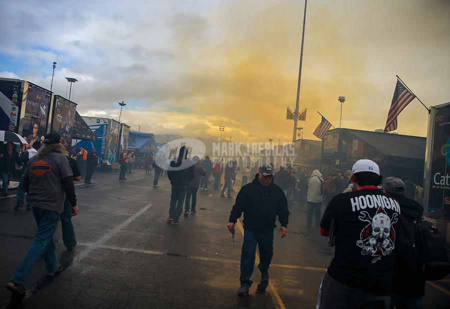 Feb 10, 2019; Pomona, CA, USA; A yellow cloud from nitromethane race fuel fumes hangs over the NHRA pit area as cars warm up prior to the Winternationals at Auto Club Raceway at Pomona. Mandatory Credit: Mark J. Rebilas-USA TODAY Sports