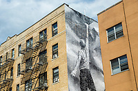 New York, NY - 9 August 2015 - Mural by street artist JR adorns the side of  a  NoLiTa apartment building in Lower Manhattan