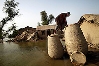 A man checks a container holding wheat to see if it has been damaged by floodwater, in the village of Gulam, Sindh Province, Pakistan.