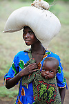 "Carrying her baby in a sling and a bag of grain on her head, a woman walks along in Chidyamanga, a village in southern Malawi that has been hard hit by drought in recent years, leading to chronic food insecurity, especially during the ""hunger season,"" when farmers are waiting for the harvest."