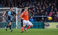 Joe Pigott of Luton Town passes under pressure from Matt Bloomfield of Wycombe Wanderers during the Sky Bet League 2 match between Wycombe Wanderers and Luton Town at Adams Park, High Wycombe, England on 6 February 2016. Photo by Andy Rowland.