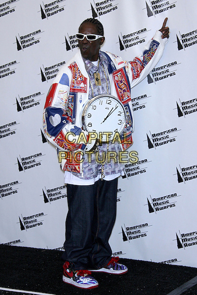 FLAVOR FLAV.34th Annual American Music Awards - Press Room held at the Shrine Auditorium, Los Angeles, California, USA..November 21st, 2006.full length watch clock necklace white red print cards sunglasses shades denim jeans pointing.CAP/ADM/ZL.©Zach Lipp/AdMedia/Capital Pictures