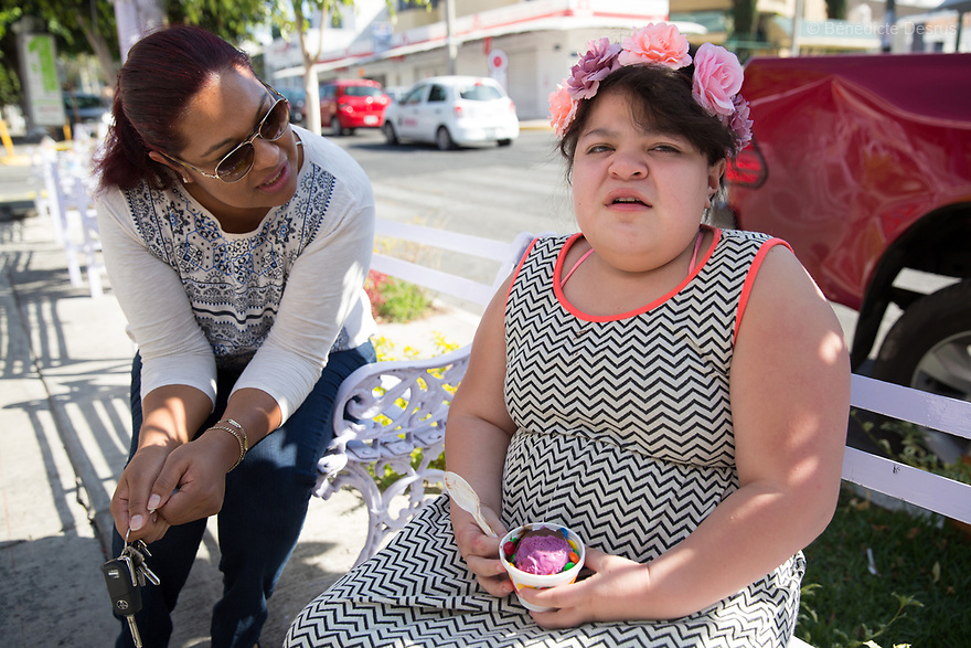 "Ana Ximena Navarro (R) and her aunt Gabriela Rios Ballesteros (L), eat an ice cream in Guadalajara, Mexico on February 22, 2017. Ximena was diagnosed as an infant with Hurler syndrome. Hurler syndrome is the most severe form of mucopolysaccharidosis type 1 (MPS1), a rare lysosomal storage disease, characterized by skeletal abnormalities, cognitive impairment, heart disease, respiratory problems, enlarged liver and spleen, characteristic facies and reduced life expectancy. Ximena was being given enzyme replacement therapy (ERT) when she was 19 months old, and she was suddenly able to eat and sleep. She is now 12, and has normal hormonal development for her age, although some mental delay, according to her father. ""Without the treatment, she would have died from all the complications — untreated, children have a very bad quality of life and typically die before they are seven"", her father says. Photo credit: Bénédicte Desrus"