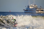 Kirsty Quigley Kamen surfs Manasquan Inlet as the Brielle party boat Jamaica heads offshore on October 21, 2012