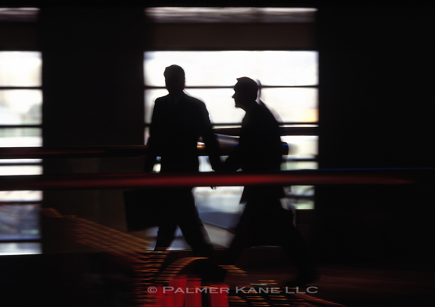 Silhouettes of business men walking in hallway