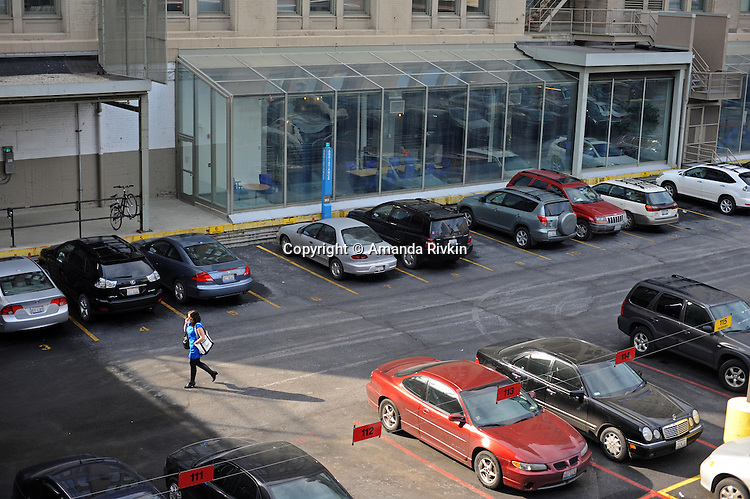 A woman walks through the Chicago Tribune parking lot, now more valuable than the paper itself, in downtown Chicago, Illinois on March 6, 2009.  With $13 billion in debt, the parking lot adjacent to The Chicago Tribune is now more valuable than the newspaper itself and is one of many assets owner Sam Zell hopes to sell, including the Chicago Cubs baseball team.