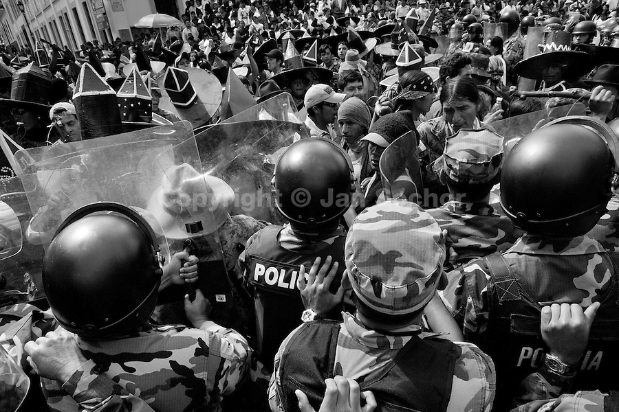 Indians clash with the riot police block during the Inti Raymi (San Juan) festivities in Cotacachi, Ecuador, 29 June 2010. 'La toma de la Plaza' (Taking of the square) is an ancient ritual kept by Andean indigenous communities. From the early morning of the feast day, various groups of San Juan dancers from remote mountain villages dance in a slow trot towards the main square of Cotacachi. Reaching the plaza, Indians start to dance around. They pound in synchronized dance rhythm, shout loudly, whistle and wave whips, showing the strength and aggression. Dancers from either the upper communities (El Topo) or the lower communities (La Calera), joined in respective coalitions, seek to conquer and dominate the square and do not let their rivals enter. If not moderated by the police in time, the high tension between groups always ends up in violent clashes.