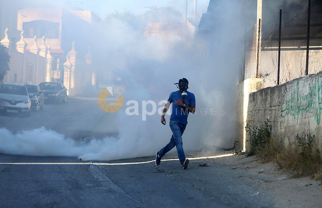 A Palestinian man runs for cover fropm tear gas during clashes with Israeli soldiers in the village of Kafr Malik, northeast of Ramallah on June 14, 2015, after clashes that resulted in the death of 21-year-old Palestinian Abdallah Ghanayem. An army spokesman said that the Palestinian had died after he threw an incendiary device at a jeep and the vehicle overturned on him. Palestinian security sources said, Israeli soldiers killed Ghanayem by hitting him with their jeep during clashes near Ramallah in the occupied West Bank. Photo by Shadi Hatem