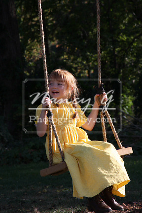 Young girl in a prairie dress on a rope swing