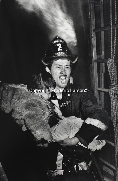 A San Francisco firefighter rescues a young child in a 4-alarm fire in the Tenderloin district  of San Francisco, California.