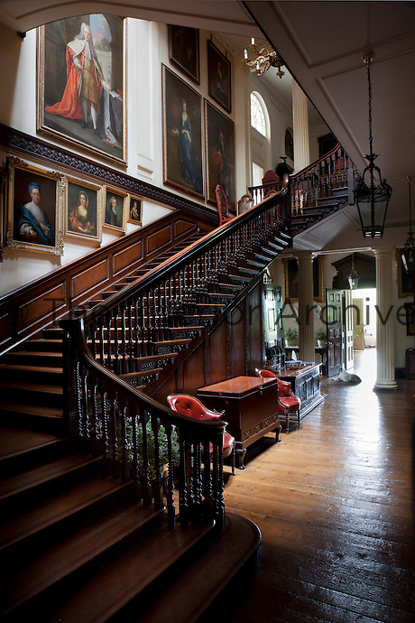 Portraits are staggered by size up the walls of the staircase designed by Wyatville