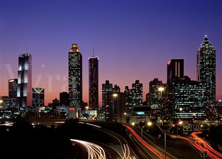 Horizontal skyline view of Atlanta at sunset; buldings in silhouette, city lights and traffic in motion. Atlanta, Georgia.