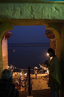 A young girl who sells flowers and candles is seen in the dark and narrow alleyways leading to the banks of the holy river Ganges where tourists come to witness the nightly Aarti prayers on the river banks in Varanasi, Uttar Pradesh, India as seen here on 18 November 2013. Guria runs a boat school targeting the boatmen's children, who are exposed and vulnerable to exploitation when they sell flowers and floating candles to the millions of tourists who come to Varanasi.