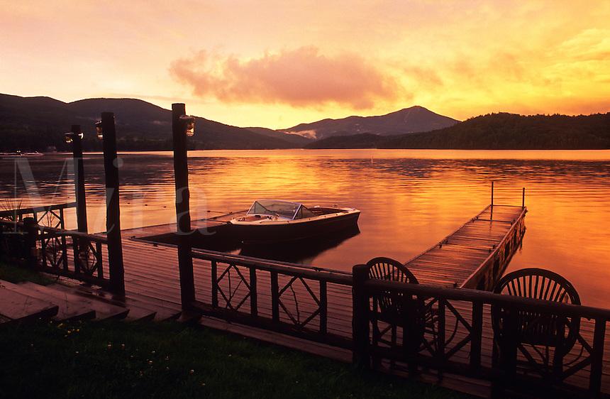 USA, New York, Lake Placid, Adirondack State Park, motor boat moored at pier at dawn.
