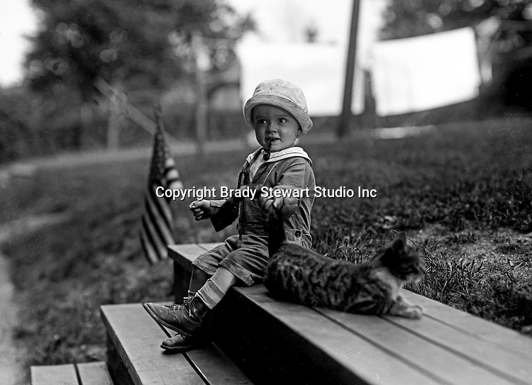 Wilkinsburg PA:  Brady Stewart Jr smoking a toy pipe and playing with the neighbors cat - 1922