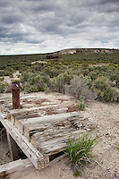 A rusty, bullet-punctuated stovepipe atop timbers of a dugout with a shed built of railroad ties in the background at the ghost town Cobre, Nevada.
